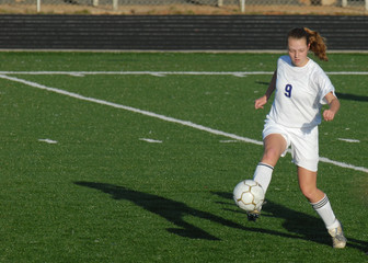 Female soccer player on green turf