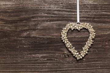 Herz aus Glocken auf Holzwand