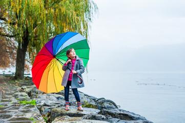 Cute little girl under big colorful umbrella