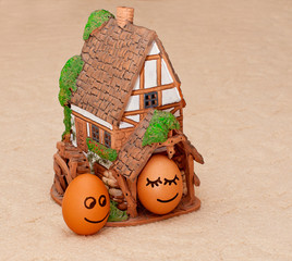 two funny smiling eggs near a house