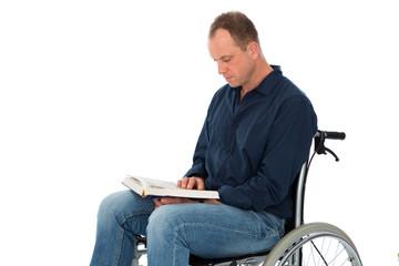 Junger Mann im Rollstuhl liest ein Buch