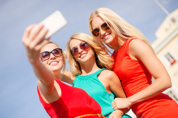 smiling girls taking photo with smartphone camera