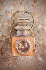 Vintage rusty lantern on a rusted steel background