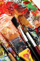 Beautiful vivid art palette and mix of paintbrushes