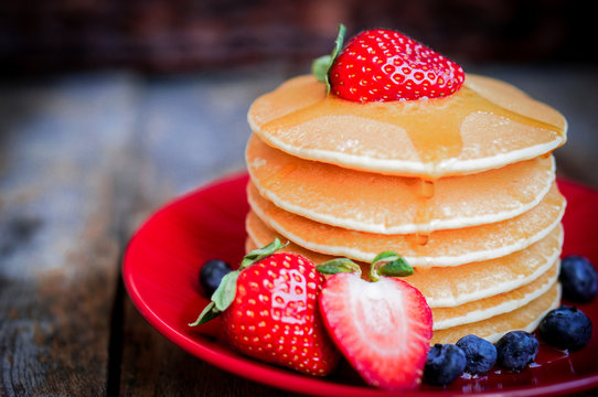 Tasty homemade pancakes with strawberries,blueberries and maple