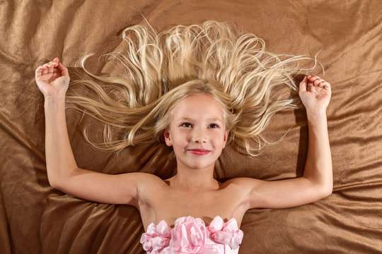 Beautiful little girl dreaming on bed