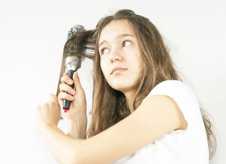 young girl combing her hair with special comb