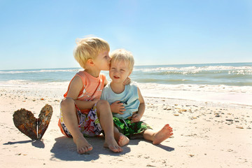 Big Brother Kissing Baby as they Sit on the Beach by the Ocean