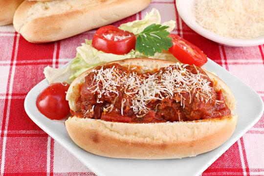Meatball parmesan sub sandwich with side salad.