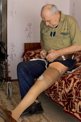 Senior man attaching a prosthetic limb to his leg