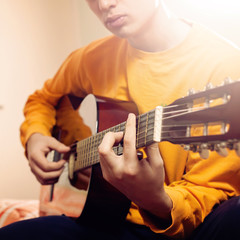 Young man playing a guitar at home and enjoys.