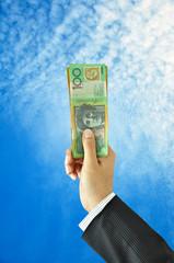 Hand holding money - Australian dollars - in blue sky background