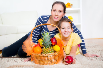 mother and daughter sit and pick fruit from the basket