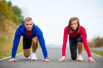 Urban leisure - woman and man ready to run
