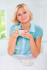 beautiful caucasian female sitting at table and drinking coffee