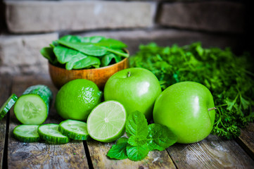 Green fruits and vegetables on wooden background