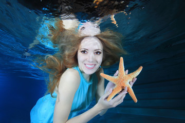 Woman underwater with sea star