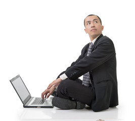 Asian businessman using laptop on ground looking back