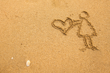 In texture of sand: girl holding a big heart.