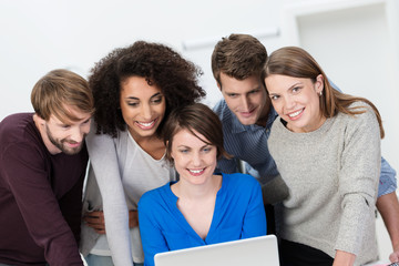 gruppe im büro schaut zusammen auf laptop