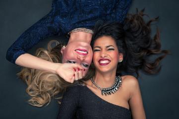Blonde and brunette women fashion portrait against black backgro