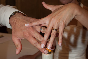 les mains des mariés le jour du mariage sur la bougie de l'église