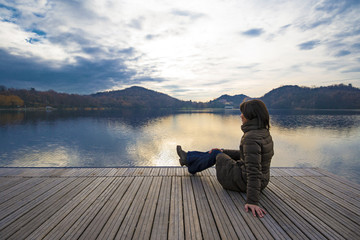 ragazza ammira paesaggio da pontile su lago Italia