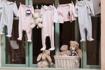 kleine baby strampler auf der wäscheleine im schaufenster