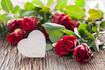 weißes Herz vor roten Rosen auf Holz