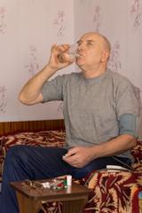 Senior man swallowing down his medication