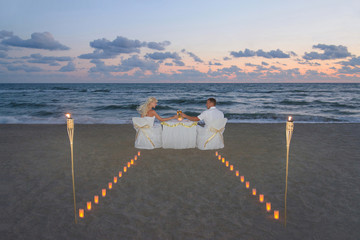 Couple at sea beach during luxury romantic dinner, decorated wit