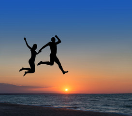 loving couple jumping highly in the sky at beach resort