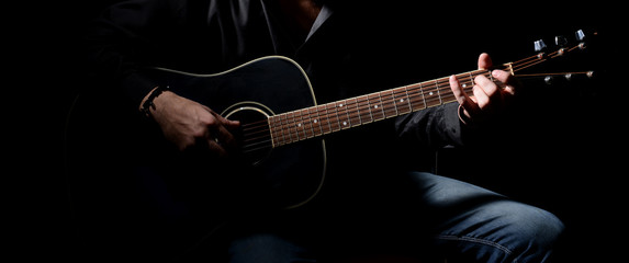 Young musician playing acoustic guitar and singing,