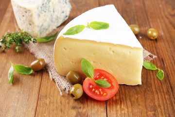 Tasty Camembert cheese with tomato, basil and olives,