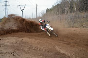 Motocross racer moves along sandy parapet turning track