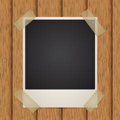 Polaroid photo, adhesive tape, wooden background