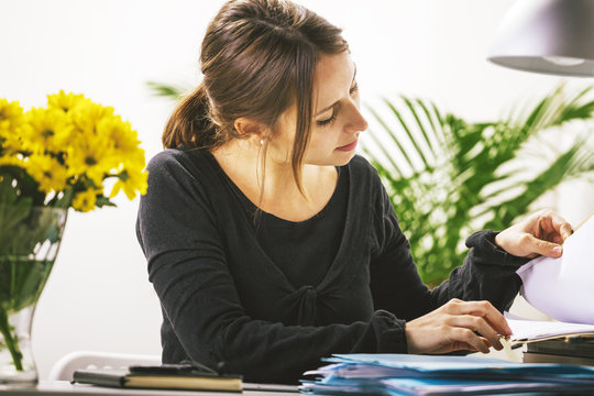 Young casual woman reviewing some documents in office.