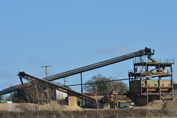 Large gravel extraction equipment with blue sky background