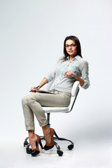 businesswoman sitting on office chair on gray background