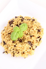 Risotto with mushrooms on a plate decorated with basil
