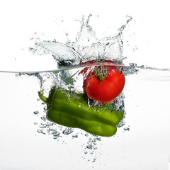 Fresh Tomato and Pepper Splash in Water Isolated on White Backgr