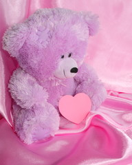 Teddy Bear & pink heart on purple silk background - stock photos