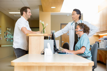 Patient With Doctor And Nurse At Reception Desk
