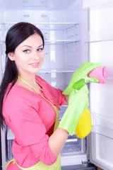 Beautiful young woman washing fridge in kitchen
