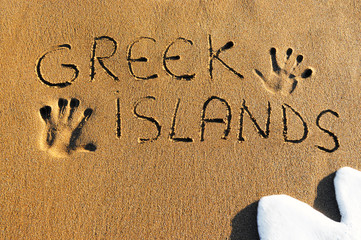Greek islands written on sandy beach