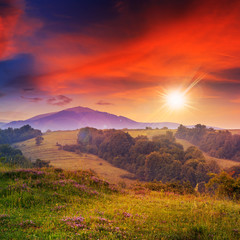 cold fog on hot sunrise in mountains at sunset