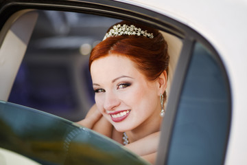 Lovely red hair bride posing with flowers outside.