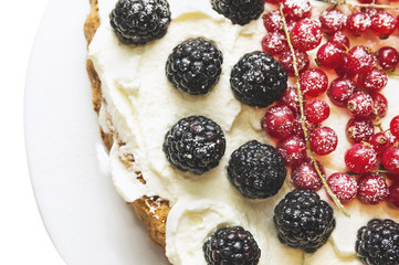 cake decoration of cream, blackberry and red currant
