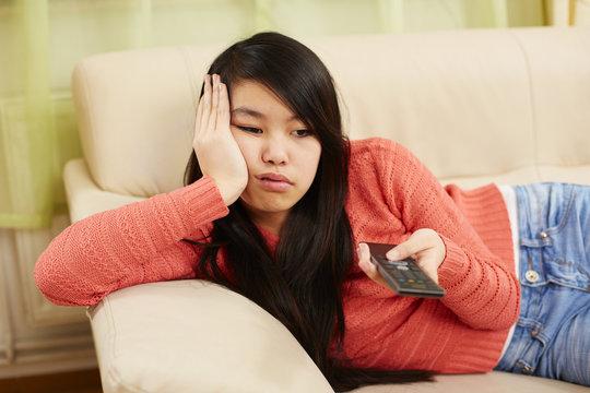 Mädchen zappt gelangweilt mit dem Fernbedienung