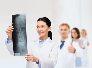 smiling female doctor looking at x-ray